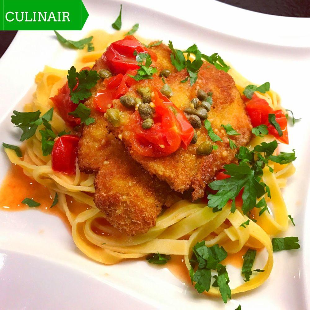 Tagliatelle met kalkoenschnitzeltjes en een saus van witte wijn tomaat citroen boter en kappertjes