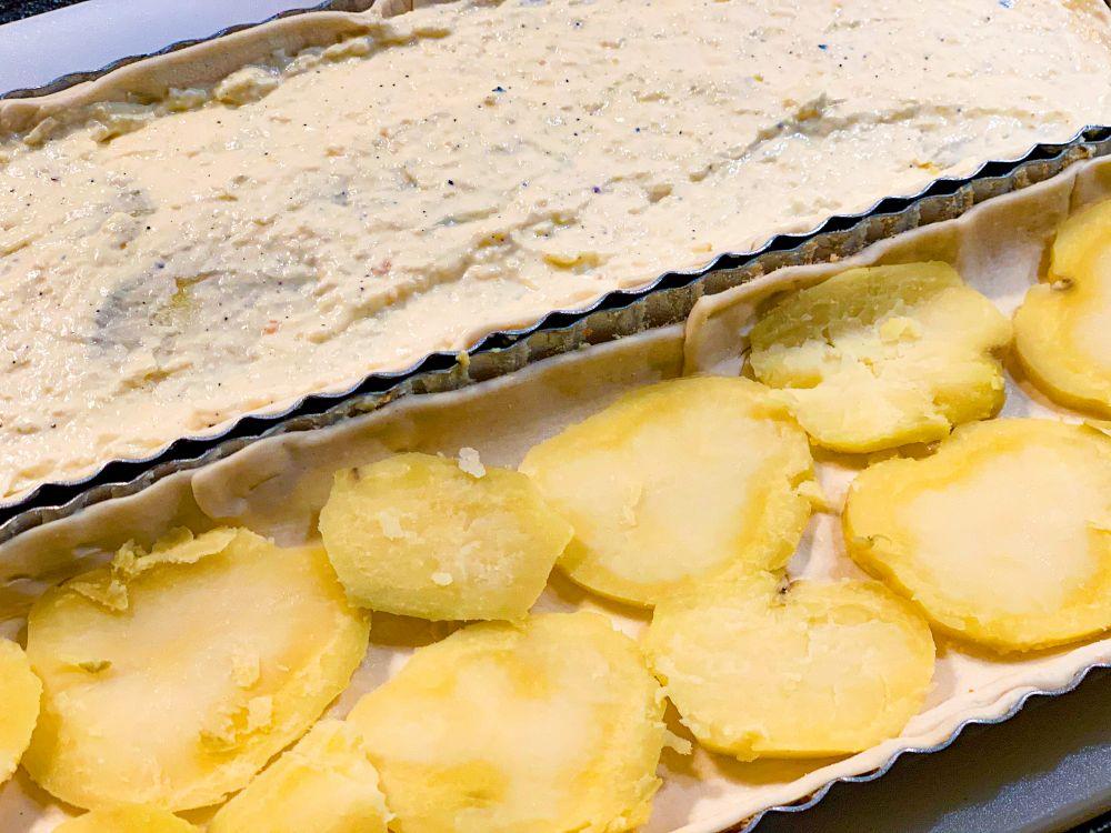 Hartige taart beleggen met aardappel en ricottamengsel
